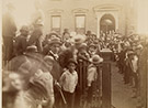 Photograph of crowd in front of Harrison's North Delaware Street home in 1888. Benjamin Harrison is standing near the front door slighlty to the left. Image shows the front of the house as it looked in 1888, picket fence at front sidewalk, and crowd of mostly men and young boys. A few women stand behind Harrison at the front door. The crowd is lined up on the rightside of the walk leading to the front door, in the yard to the left, and on the front sidewalk to the left.