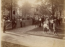 Photograph of crowd in front of Harrison's North Delaware Street home in 1888. Wider view showing crowd in front of Delaware Street home and showing the houses to the north. Brick driveway and sidewalk in foreground.
