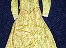 Gold flowered silk one piece dress marked as being Caroline Harrison's. Fabric is a gold color and different shades outlined in black of a design of long stemmed flowers. Like a poppy or daisy. Lace trimmed collar and cuffs. Lined, bottom edge of skirt inside small ruffle of a stiff netting. 13 buttons on front of bodice. Bodice attached at back with skirt. Metal stays some coming through fabric.