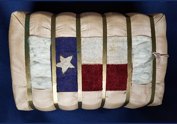 This small bale of cotton was presented to Mrs. Harrison during a Presidential visit to Galveston, Texas, April 18, 1891. It is covered on all sides with a grosgrain silk fabric, but the fabric comes around the two wide sides partially leaving a small