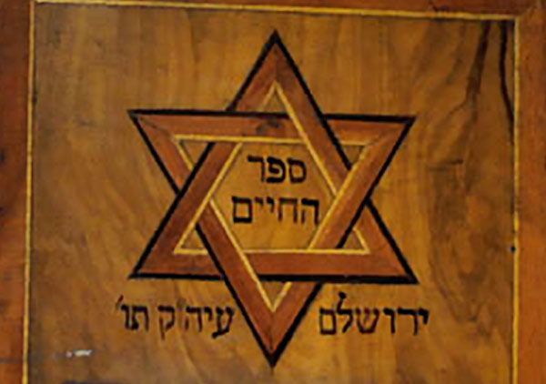 Hebrew book with wood cover with inlaid design and carving. Carved temple at bottom front, above is an inlaid Star of David.