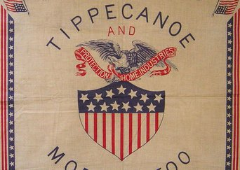 A design printed on cloth from the Benjamin Harrison home. The design is lined by stars and stripes, with two american flags protecting the corners. The center is an illustration of a bald eagle holding a piece of cloth in its mouth that reads