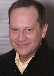 Portrait of Ken Eder, a middle aged man with dark brown hair and dark eyes. He wears a black jacket with lightly colored undershirt, and a smile.