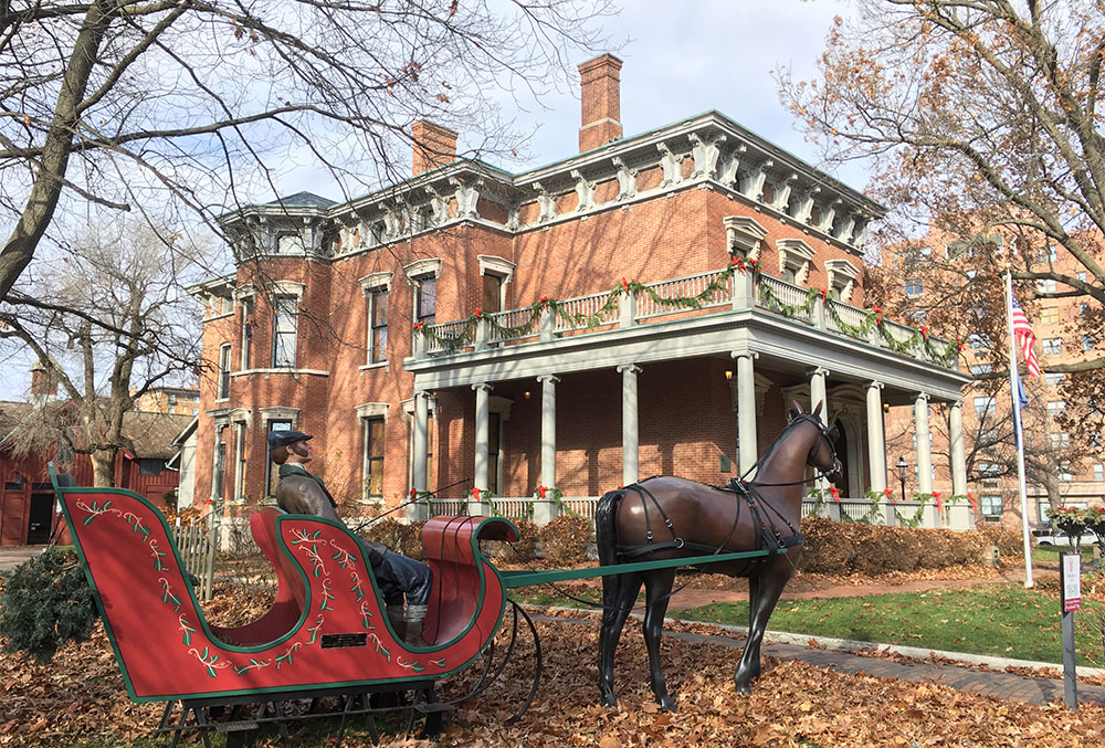 outdoor photograph of the mansion during late december, circa 2018. Photograph shows a sleigh being pulled by a horse in front of the mansion.