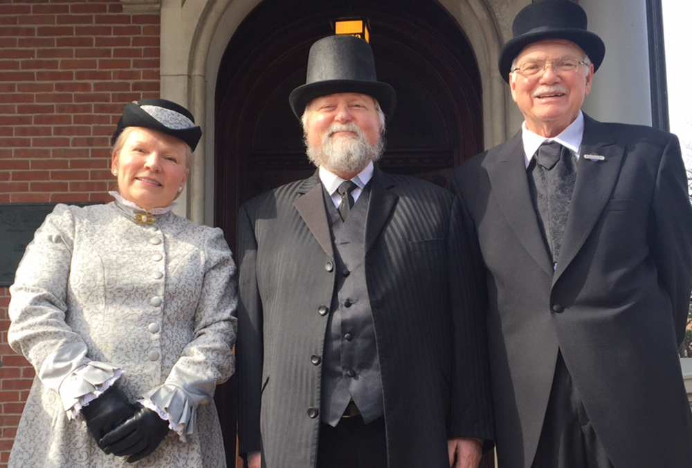 Photographic image of reenactors dressed as the Harrison family, and posed in front of the front doors of the presidential mansion.
