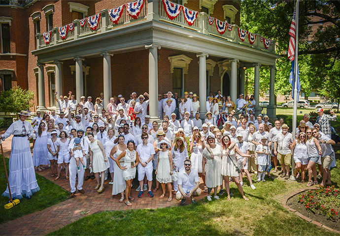 Photographic image of a large group of people dressed in white croquet clothes in front of the Harrison mansion.