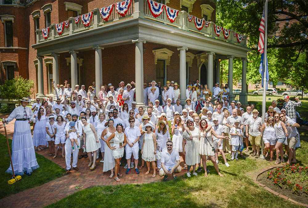 Photograph of a large group of people dressed in white in front of the Harrison mansion.