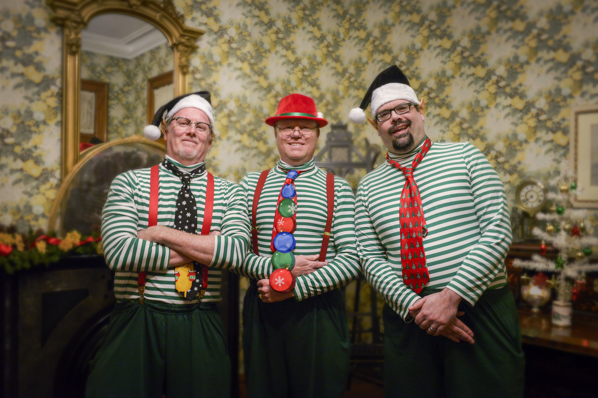 Photo of three men dressed like festive elves inside the Benjamin Harrison Home.