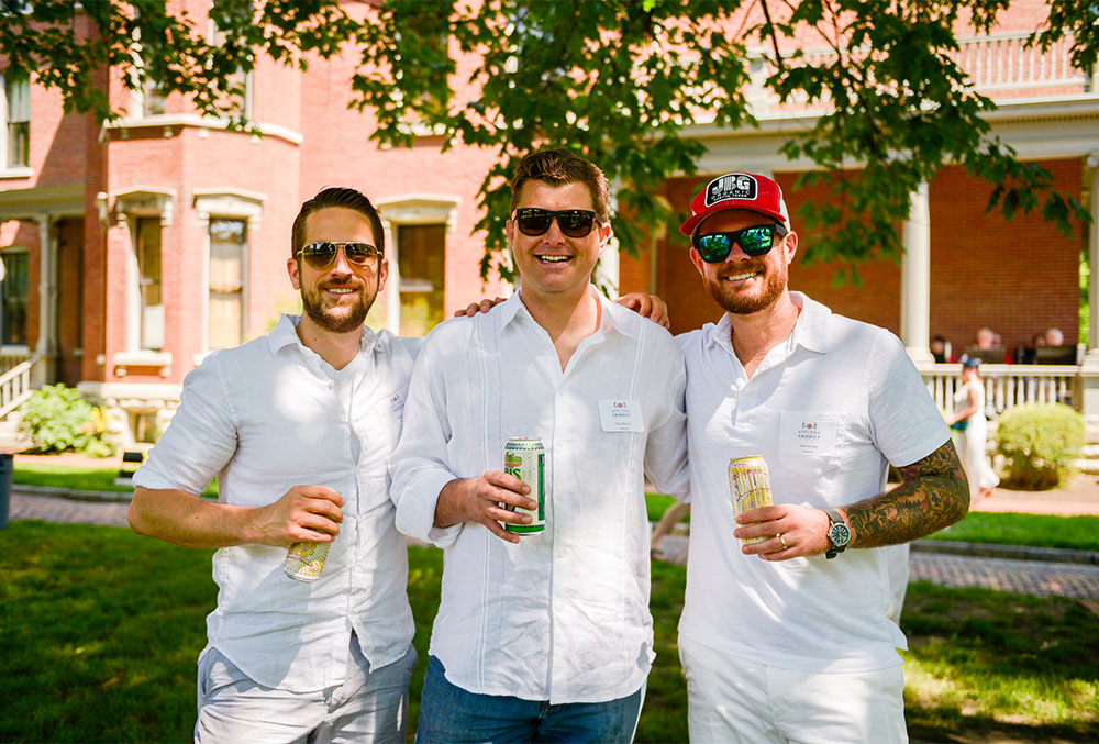 Photograph of a trio of males having a good time at the Presidential Site, all dressed in white, sporting sunglasses, holding drink cans, and relaxing in the shade of an oak tree in the side yard.