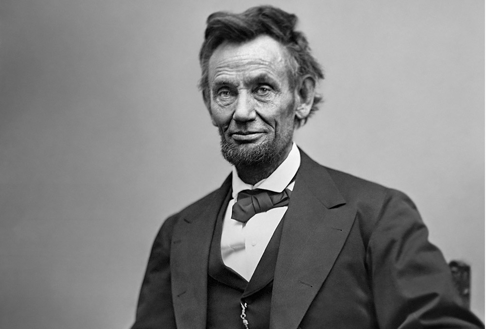 Photograph of Abraham Lincoln, whom wears a slight smile on his aged face.