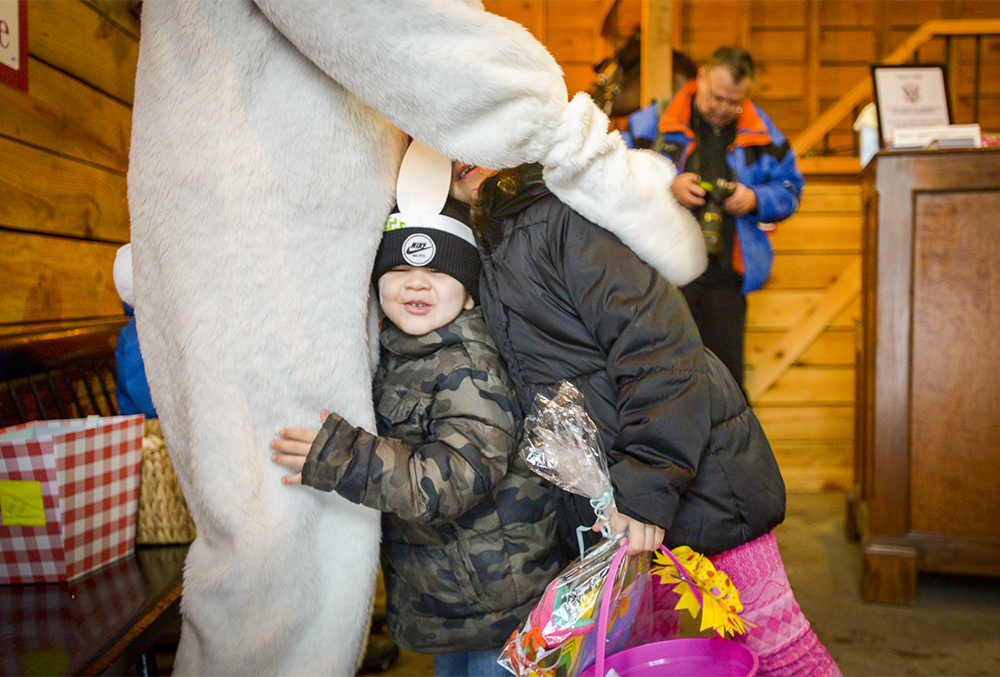 photograph of a child hugging the easter bunny's leg at the presidential egg roll easter event.
