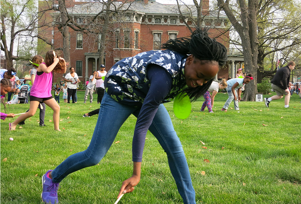 Photographic image of a girl playing egg roll on the lawn of the presidential site.