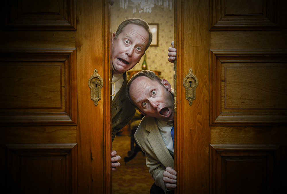 Photograph of two surprise men looking around the edge of a door.