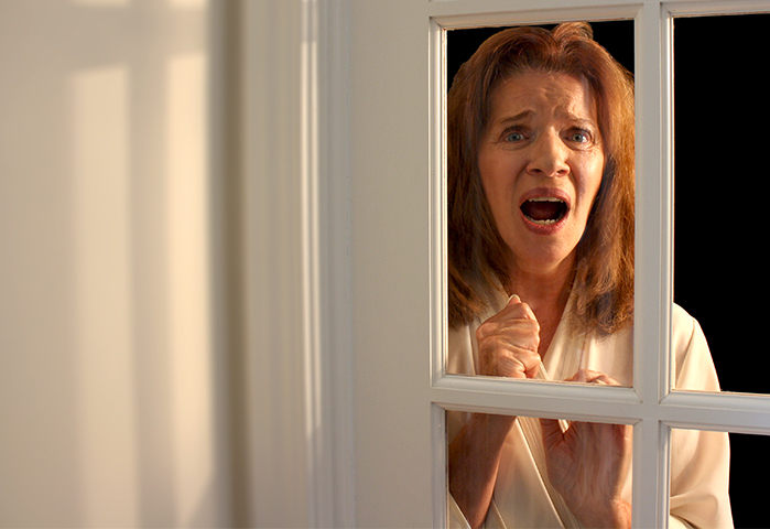 Photograph of a scared woman looking out of a window.