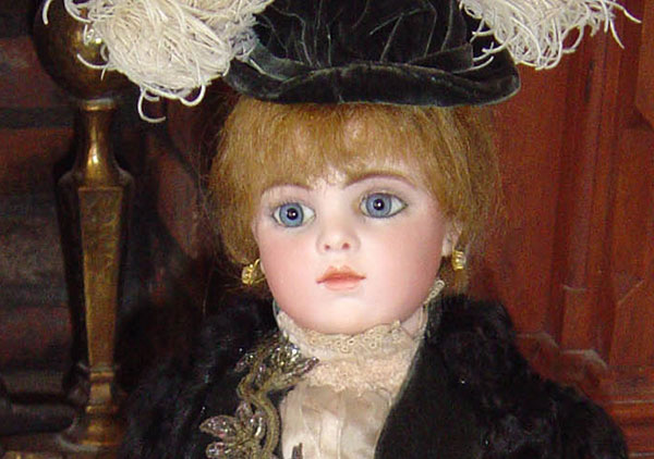 This close up photograph of the doll shows some finer details of the face, hat, and dress. Doll has Blonde hair and blue glass eyes. Her head shoulders, and forearm are bisque with upper arms & body thighs are kidskin leather. The lower legs and feet are celluloid. Tiffany mounted, fake pearl pierced earrings hand from her pierced ears. She is wearing a late nineteenth century style black dress with a feathered hat.
