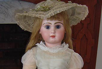 Photo of Baby Mckee's jumeau doll. The head is bisque and composition body has jointed arms and legs, blue glass eyes and long curled blond hair. The doll has pierced ears with imitation ruby earrings.