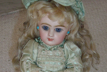 "Jumeau doll is 16"" tall with original satin dress, leather shoes, earrings, and hat. Her body is molded body with a bisque head. Head marked"