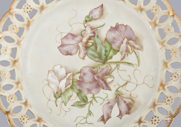 Photograph of plate with hand painted sweet peas. Edge is a cutout lace pattern with gold paint. Called a ribbon plate because ribbon could be put through border to hand on wall.