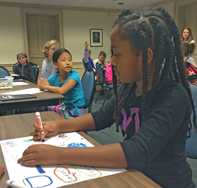 Image of a young girl drawing in a classroom with other students in the background.