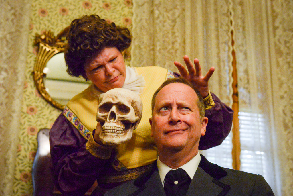 photo of two comedies of error actors. a woman is standing on the left, holding a human skull and holding a hand above a seated man's head while he has a curious expression on his face.