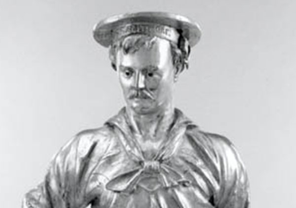 Full figure of a man in sailors uniform with hat. Figure has right hand on hip and left hand at side. Base has inscription