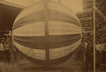 Photograph (sepia tone) mounted on heavy board. Images shows 1888 Campaign Ball with D. E. Brockett (designer and builder) standing to the left with other men behind him and to the right side of the ball. There is also a stack of lumber to the back on the right and a shed type building to the left. Below image on board is the following information: