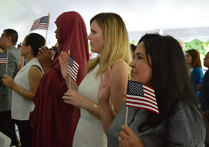 Photograph of a crowd of people holding small american flags in their hands.