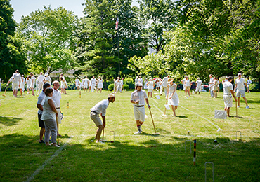 Image of 30 people dressed in white playing croquet on a green lawn
