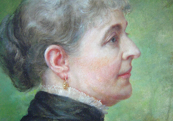 Oil on canvas by Lilly M. Spencer (Lilly Martin Spencer) of Caroline Scott Harrison in profile view. Spencer signature is in lower left (not visible when portrait is in frame). Many engravings and prints were made from this image of Caroline Harrison. She is wearing a dark dress with white lace trim at the high neck, gold earrings, and hair is pulled back in a bun. Background is green in varying dark to medium shades. Pat. date of 1885 on metal corner brackets of wooden stretcher.