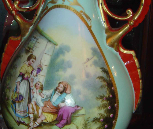 Porcelain blue vases, gold trim and orange-red handles. Hand painted street scenes with child on man's lap and woman holding grapes. Wedding gifts from Mrs. Harrison's father, John W. Scott, to Mrs. William Bridges about 1874-75.