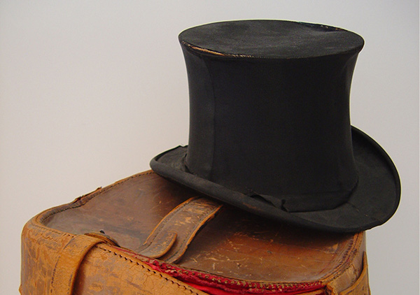 Benjamin Harrison's silk top hat on top of a leather carrying case. Black satin or silk hat. the hat is 6 inches tall with a slight bowed flare toward the middle the stack; seams on both sides; a band to cover the joining of stack and brim is missing except on the right front; a partial bow is placed on the right side; stitches are showing where band would have been.