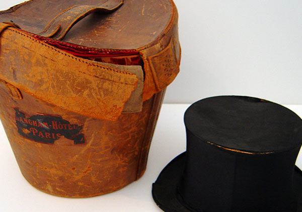 Leather carrying case for Benjamin Harrison's top hat. Case: Leather shows signs of red rot. Straps broken, rim of lid coming detached from both sides, and general marks and scuffs on leather. Harrison's black silken top hat lays next to the case for scale and reference.