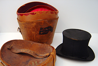 Opened view of the top hat case. Shows a red velvet interior shaped to accommodate the hat.