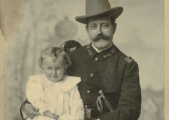 Photo of Russell Benjamin Harrison and his son. Russel is seen wearing a military uniform, with a sword at his side and a brimmed hat on his head. His son is dressed in all white.