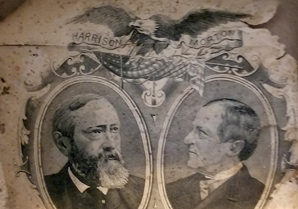 Photograph of the inside of the top hat used in benjamin harrison and levi morton's campaign, which bears a portrait of each of them decoratively framed above the white house with a bald eagle watching over. Inside at top of hat is a paper showing images of Benjamin Harrison on the left and Levi P. Morton on the right. Top center of paper is an eagle and bottom is image of White House. The paper is torn at top right and has brown spots.