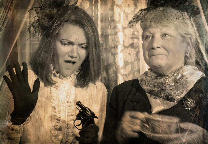 Candlelight theatre actors mid-performance. One actor on the left, a young woman, is wearing nineteen forties era dress, black gloves, and surprise at a snubnosed revolver she is holding. The actor on her right, an older woman, warmly smiling into the distance and holding a tea cup on a saucer.
