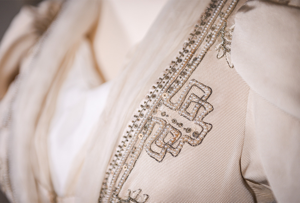 Photograph of the breast portion of a late nineteenth century dress. the dress is pink and accented by an intricate pattern in a slightly darker tone.