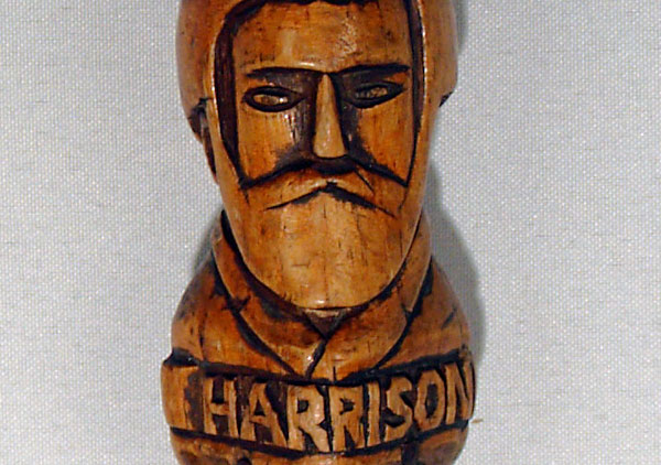 Centennial walking stick, contains hand carved images (head and shoulders in relief) of all the Presidents from Washington to Benjamin Harrison with name below each. They are on both sides of the cane coming down to Harrison. Wood is white pine and stained. The carved handle is an animal head design. Three of the president's names are misspelled: Madison, Hayes, and Arthur.