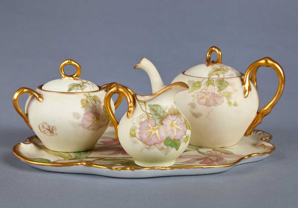 Photograph of luxury china set. The set includes a gold lined tray with a floral pattern, complete with a matching kettle and two small jugs.