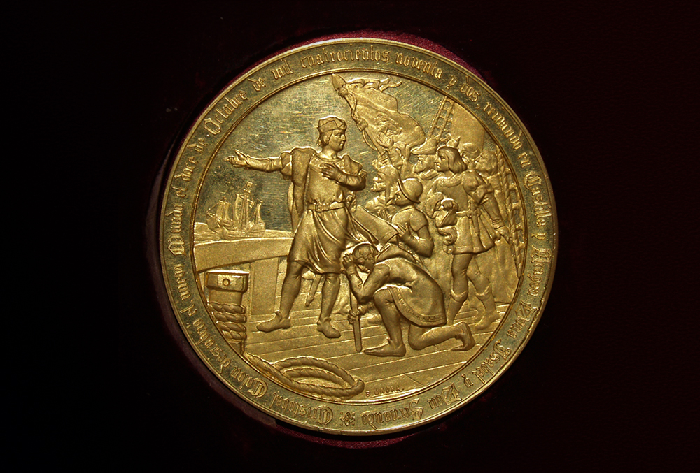 Photograph of a gold coin. The coin features an engraving depicting george washington speaking to troops during the revolutionary war, one of which kneels at his feet while the others carry a tattered flag.