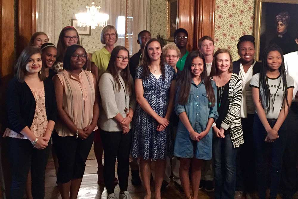 Lieutenant Governor Suzanne Crouch poses with students in the back parlor of the Harrison Home.