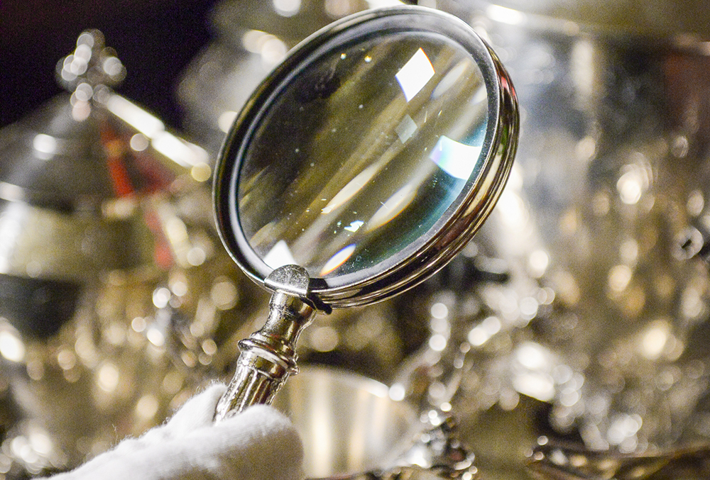 Photograph of a magnifying glass being held by a gloved hand in front of a blurry background.