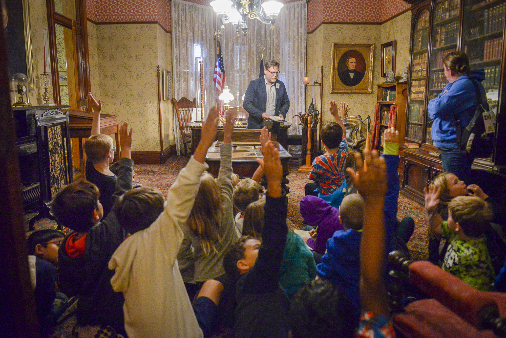 Students raising hands at a Presidential Site tour, in the office of Benjamin Harrison.