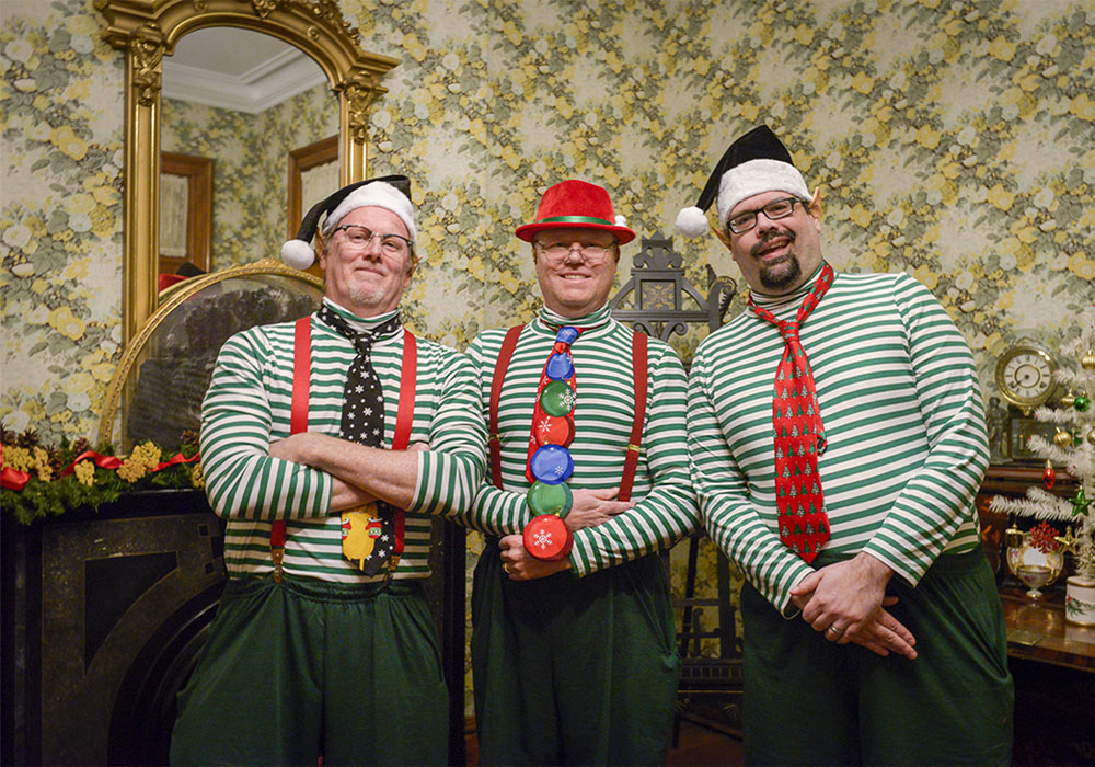 Photo of three men dressed as festive elves during a holiday event at the candlelight theater.