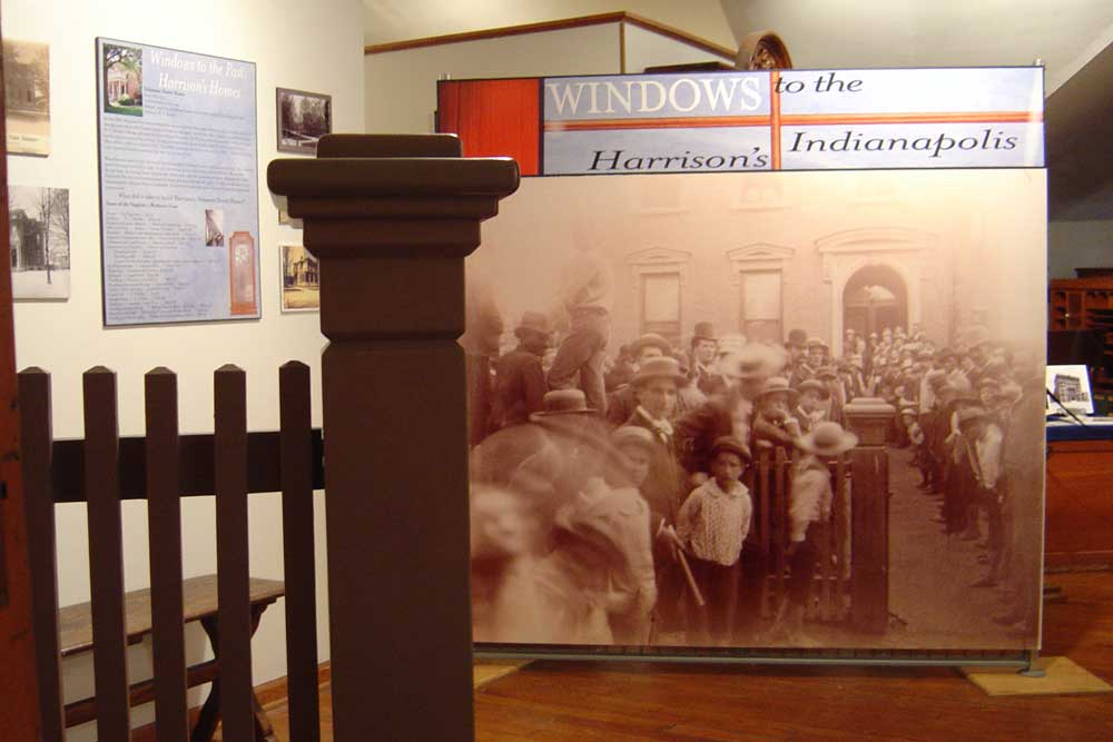 a photograph from the third floor of the benjamin harrison home, showing a railing and some photography from the eighteen hundreds of a large crowd gathered outside the presidential home.