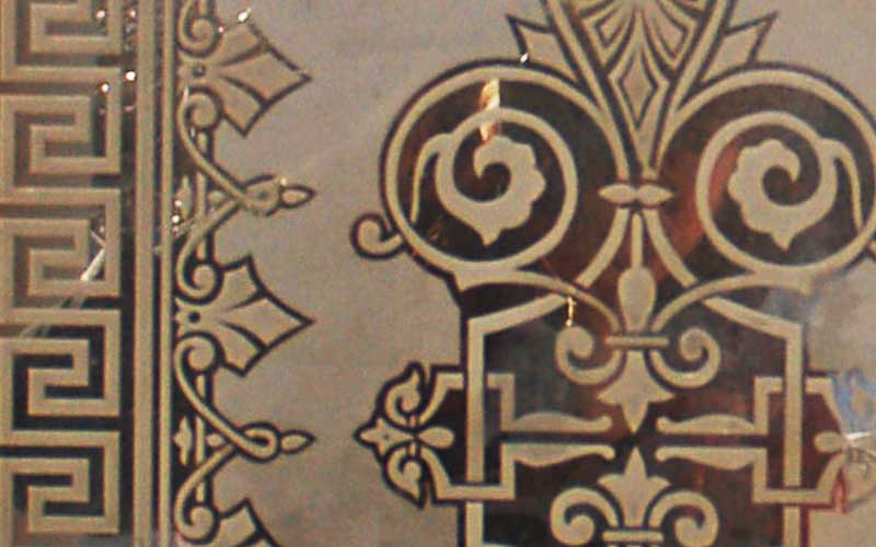 Closeup of the engraved glass on the door. Shows french style patterning with curves and hard edges.