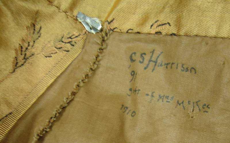 This close up of Caroline's gold dress shows an inscription on the inside that reads,