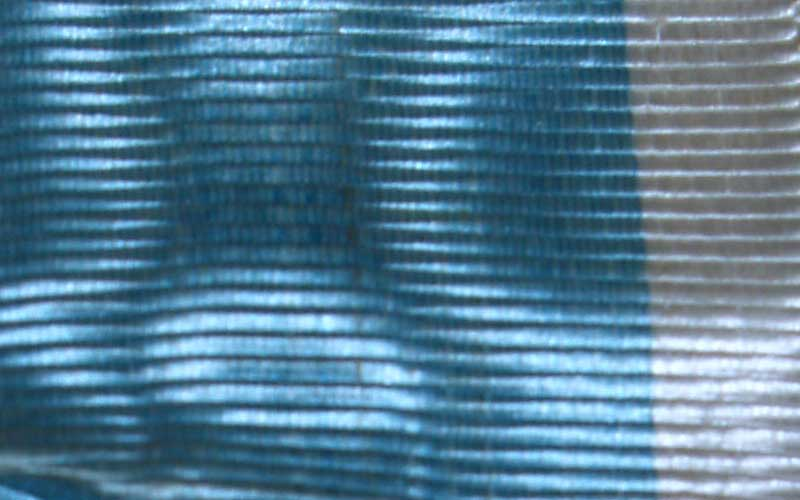 Closeup on the ribbon on the metal. Appears to be a sleek blue and white fabric with light bouncing off.