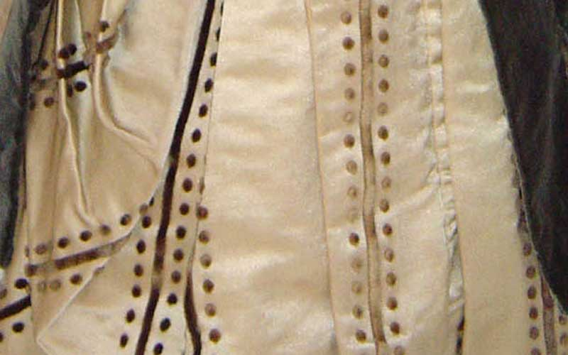 Photograph showing finer details on the dress skirt. There skirt is ornately connected with buttons and lining the accents vertically, in gold. The fabric is lightly wrinkled.