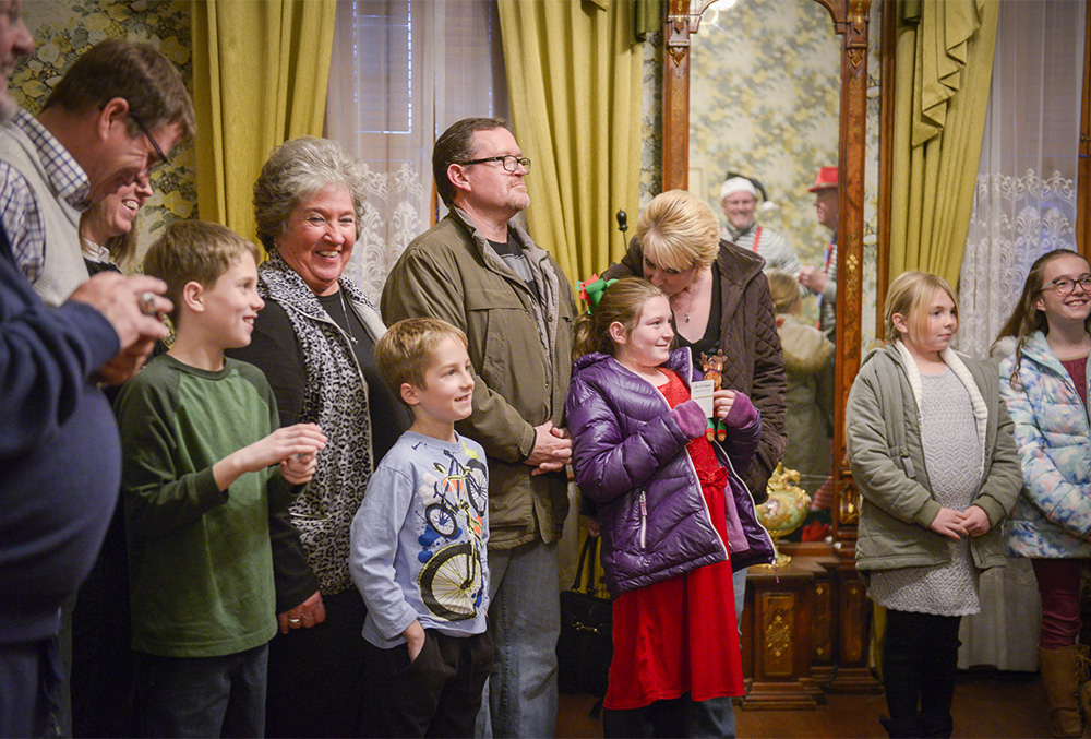 Photo of a smiling family gathered in the Benjamin Harrison Home during the Candlelight Theatre.